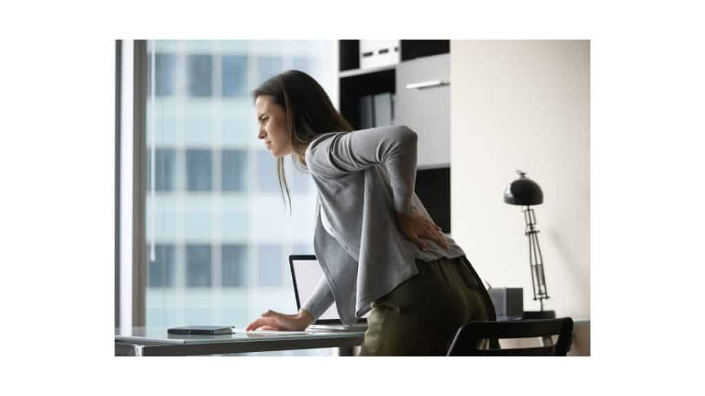 Woman bent over in pain on desk bracing her lower back sciatic pain.